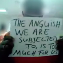 An inmate holding a sign saying The Anguish we are subjected to is too much for us