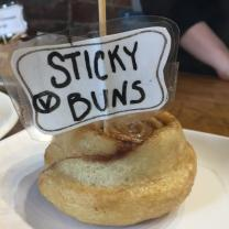 A cinnamon bun with a sign on it saying Sticky Buns
