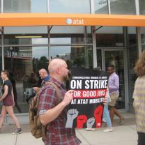 Guy in a strike protest holding a sign that says On Strike