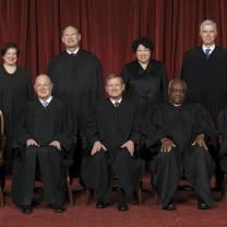 Photo of men and women posing and facing the camera all wearing long black robes in front of a dark red curtain