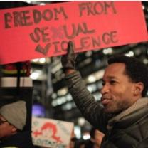 Black man holding a sign that says Freedom from Sexual Violence