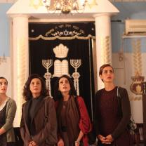 Four women staring up at something above them, standing in front of an elaborately decorated doorway