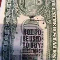 A close up of the back of a dollar bill with a stamp on it saying Not to be used to buy elections