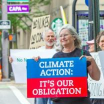Woman holding a sign saying Climate Action It's our Obligation