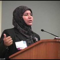 Muslim woman speaking at a mic