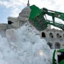 Big white stately building with round top and lots of windows behind a huge green truck with a big arm and huge shovel putting a ton of white snow in a big pile in front